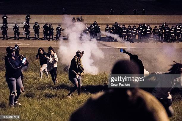 Protestors run from a gas canister after blocking traffic on the I85 during protests in the early hours of September 21 2016 in Charlotte North...