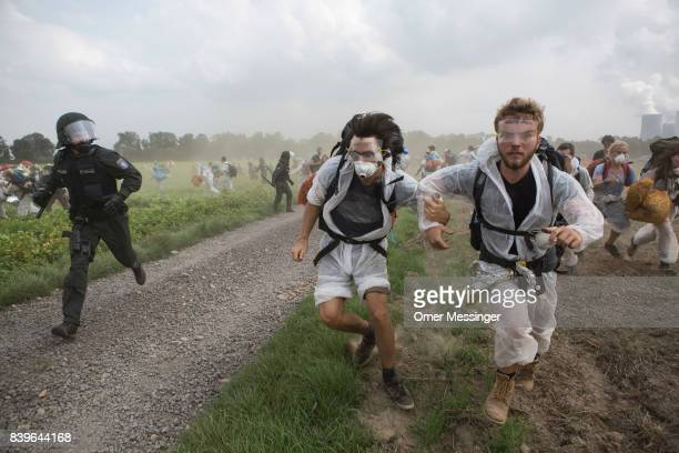Protestors run from the German police in the Rhineland mines region west of Cologne on August 26 2017 near the German village of Rath Germany...