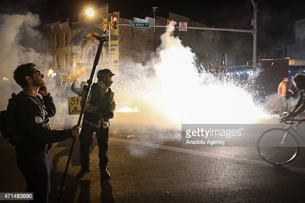 Protestors run to avoid pepper spray fired by riot police during a curfew in Baltimore, Maryland, USA on 28 April 2015. Tensions eased on 28 April...