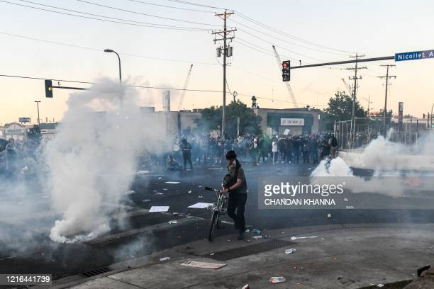 Protestors run to take cover as police start firing tear gas and rubber bullets near the 5th police precinct during a demonstration to call for...