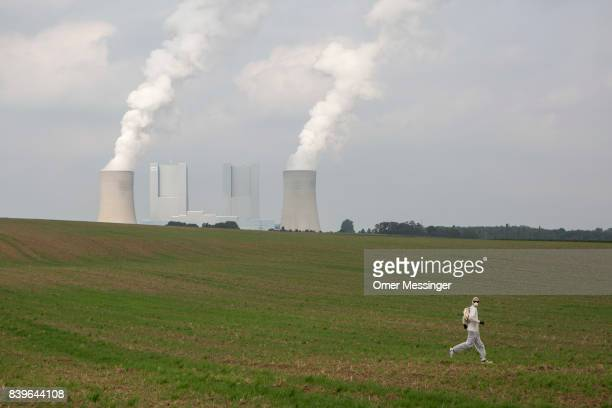 A protestors runs through a field to avoid German police with the RWE Power AG power plant in the background in the Rhineland mines region west of...