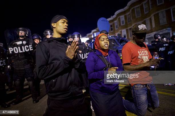 Protestors say the Lord's Prayer beside riot police the night after citywide riots over the death of Freddie Gray on April 28, 2015 in Baltimore,...