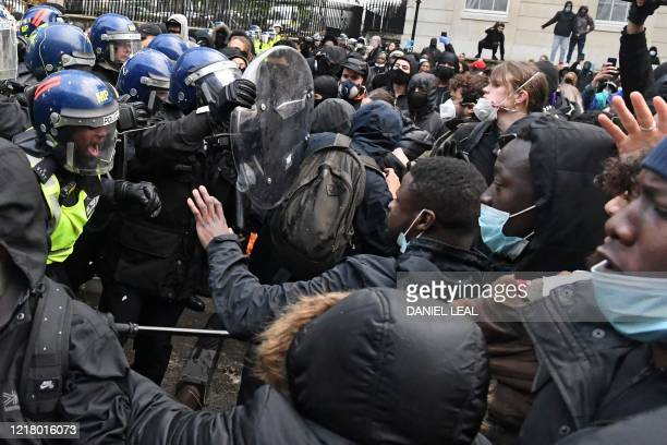 Protestors scuffle with Police officers in riot gear near Downing Street in central London on June 6 during a demonstration organised to show...