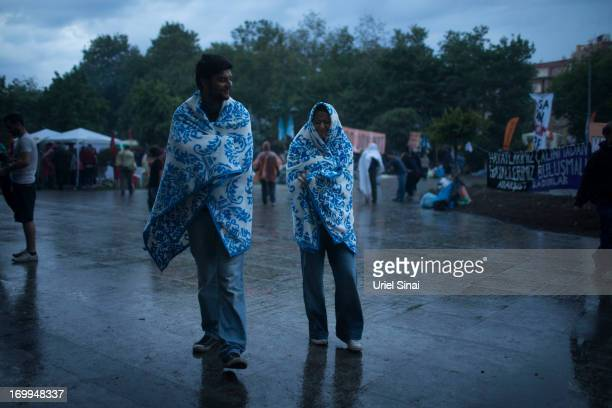 Protestors shield from the rain as morning breaks at the Gezi park in Taksim Squareon June 5 2013 in Istanbul Turkey The protests began initially...