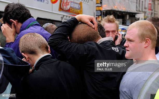 Protestors shield their faces from the cameras as British riot police attempt to control clashes between members of the English Defence League and...