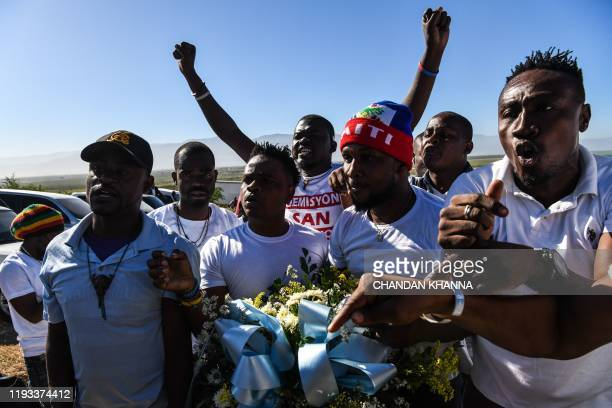 Protestors shout antigovernment slogans outside the mass graveyard during the commemorative ceremonies of Haiti's 10th earthquake anniversary on the...