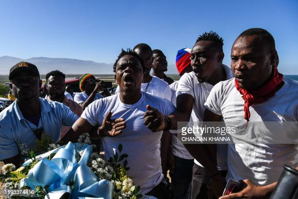 Protestors shout anti-government slogans outside the mass graveyard during the commemorative ceremonies of Haiti's 10th earthquake anniversary on the...