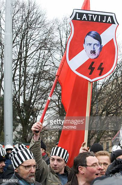 Protestors shout as former veterans of the Latvian Legion a force that was part of the Nazi German Waffen SS walk with relatives to the Monument of...