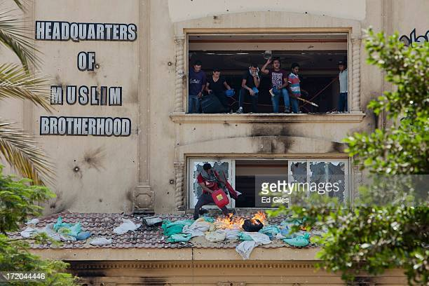 Protestors shout from the windows of the headquarters of Egypt's Muslim Brotherhood as they set fire to debris and ransack the building in the suburb...