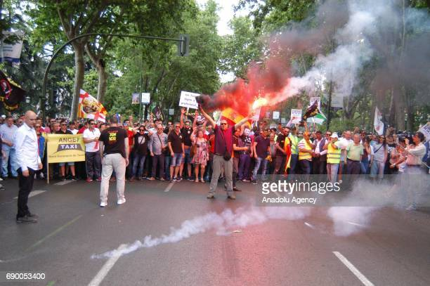 Protestors shout slogans and throw smoke cannisters during taxi drivers' national strike in Madrid Spain on May 30 2017 Taxi drivers went to general...
