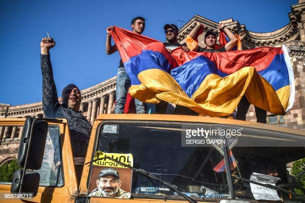 Protestors shout slogans and wave an Armenian national flag as they stand on a truck with a photograph of Armenian opposition leader Nikol Pashinyan...