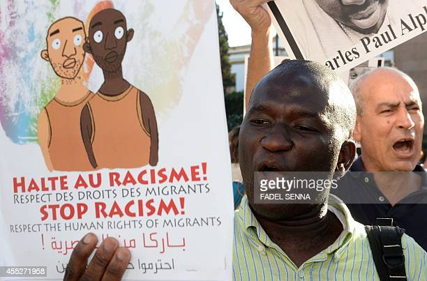Protestors shout slogans as they hold placards during a demonstration in Rabat on September 11, 2014 against racism in Morocco after the murder of a...