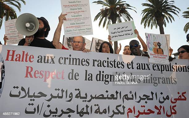 Protestors shout slogans as they hold placards during a demonstration in Rabat on September 11 2014 against racism in Morocco after the murder of a...