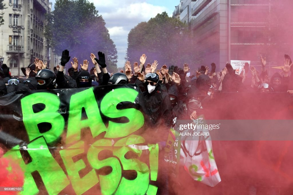 Protestors shout slogans as they march behind a banner as smoke from flares rises during a demonstration on the sidelines of a march for the annual May Day workers' rally in Paris on May 1, 2018.