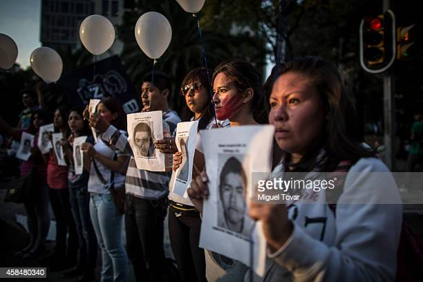 Protestors show pictures of disappeared students in Ayotzninapa on Reforma Avenue during a demonstration to ask for justice for the 43 missing...