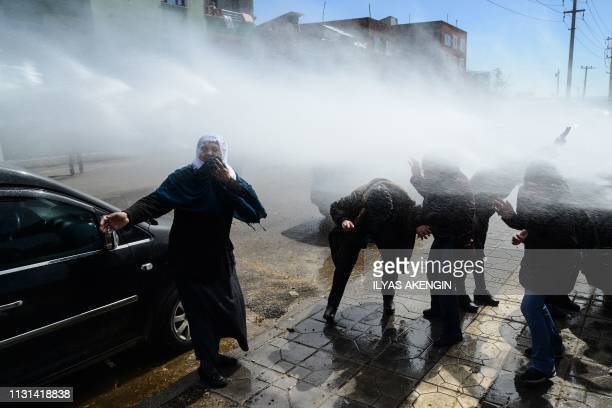 Protestors sing victory as Turkish antiriot police officers use water cannon during Kurdish activist Zulkuf Gezen funeral in the Turkish city of...