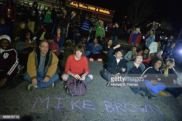 Protestors sit in the street outside the Ferguson Police Department on March11 2015 in Ferguson MO Protests erupted after the announcement of the...