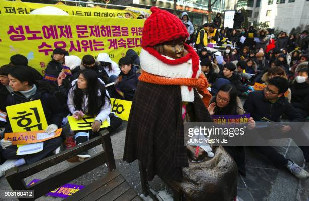 Protestors sit next ot the statue of a teenage girl symbolizing former comfort women who served as sex slaves for Japanese soldiers during World War...