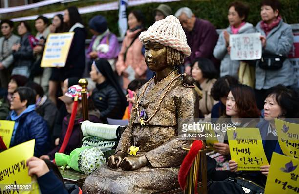 Protestors sit next to a statue of a South Korean teenage girl in traditional costume called the 'peace monument' for former 'comfort women' who...
