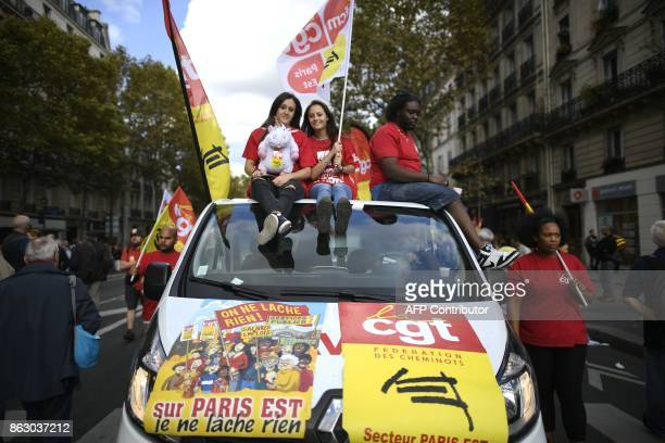 Protestors sit on a vehicle during a demonstration called by the General Confederation of Labour French worker's union in Paris on October 19 part of...