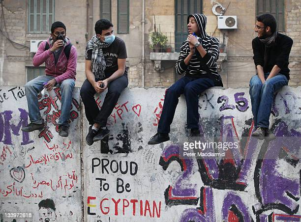 Protestors sit on a wall in Mohammed Mahmoud Street near Tahrir Square after police withdrew on November 23 2011 in Cairo Egypt Thousands of...
