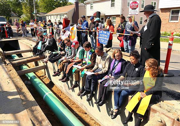 Protestors sit on the edge of the exacted street above a 16inch gas pipeline being laid five feet below the street in Boston's Roxbury neighborhood...