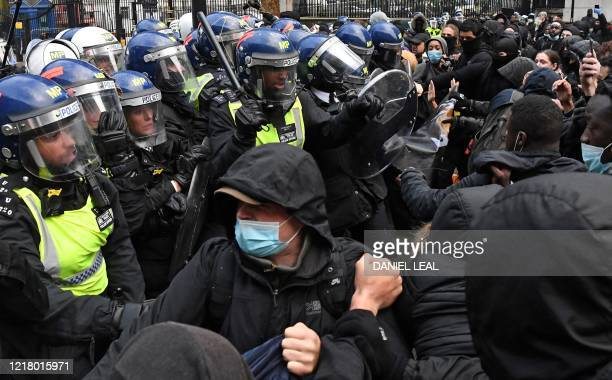 Protestors some wearing PPE including a face mask as a precautionary measure against COVID19 scuffle with Police officers in riot gear near Downing...