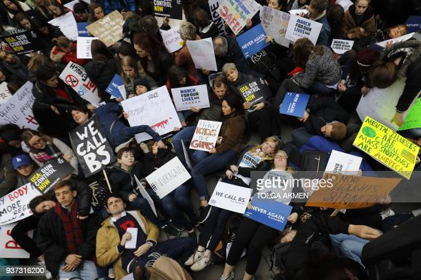 TOPSHOT Protestors stage a 'diein' during a demonstration calling for greater gun control outside the US Embassy in south London on March 24 2018 The...