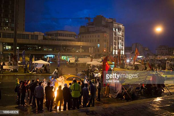 Protestors stand by a fire as morning breaks at the Gezi park in Taksim Squareon June 5 2013 in Istanbul Turkey The protests began initially over the...