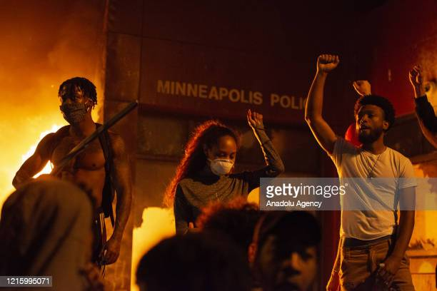 Protestors stand fists raised in front of the burning Minneapolis 3rd police precinct on Thursday May 28 during the third day of protests over the...