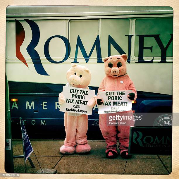 Protestors stand in front of a campaign bus outside a rally for Republican presidential candidate Mitt Romney in New Hampshire