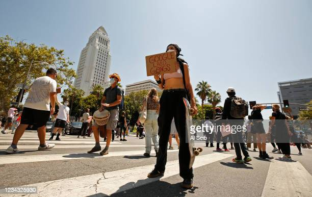 Protestors stand in front of vehicles briefly shutting down the intersection of Spring and 1st Streets in downtown Los Angeles after the group...
