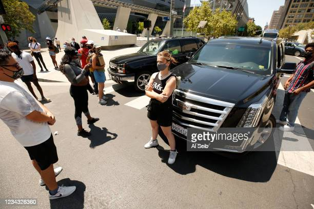 Protestors stand in front of vehicles briefly shutting down the intersection of Main and 1st Streets in downtown Los Angeles after the group gathered...