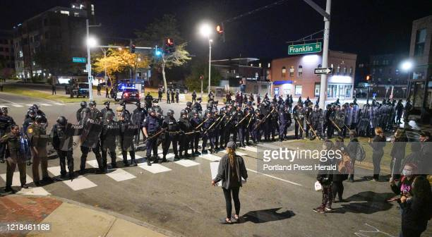Protestors stand near a line of police in riot gear on Franklin Arterial on Tuesday night.