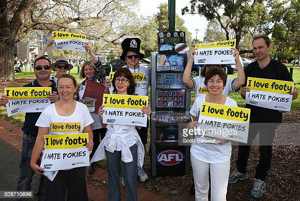 Protestors stand near a replica poker machine that shows how much Carlton and Collingwood reap from poker machines each week during a pokies protest...