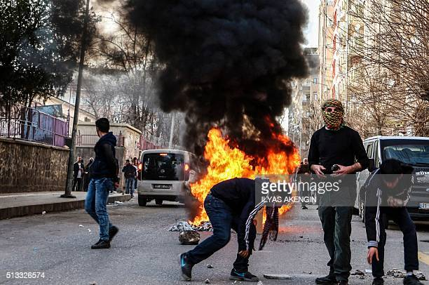 Protestors stand next to a fire during clashes between Turkish forces and Kurdish people in the centre of Diyarbakir as they protest against the...