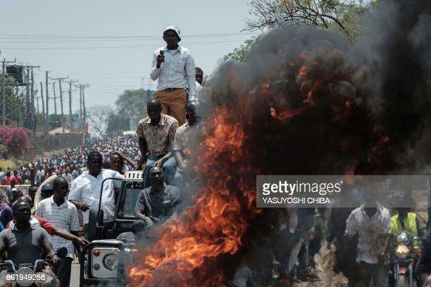TOPSHOT Protestors stand on a car by a fire as they take part in a demonstration on October 16 in Kisumu to demand the removal of officials from the...