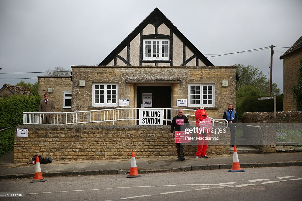 Protestors stand outside a polling station ahead of the arrival of Prime Minister David Cameron on May 6, 2015 in Spelsbury, England. The United Kingdom has gone to the polls to vote for a new government in one of the most closely fought General Elections in recent history. With the result too close to call it is anticipated that there will be no overall clear majority winner and a coalition government will have to be formed once again.
