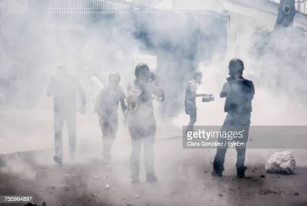 protestors standing in smoke - venezuela stock pictures, royalty-free photos & images