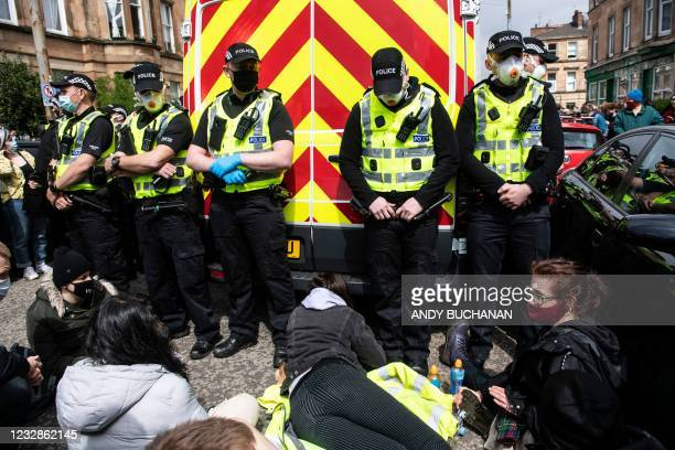 Protestors surround an Immigration Enforcement van to stop it from departing after individuals were detained in Glasgow on May 13, 2021.