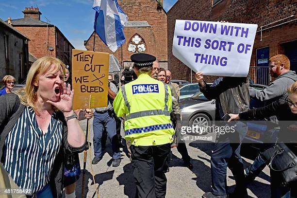 Protestors surround the car of Scotland's only Conservative MP David Mundell following his opening of a foodbank at the Apex Centre to help people...