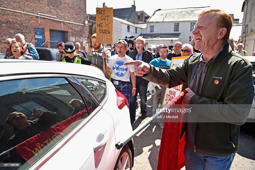 Protestors surround the car of Scotland's only Conservative MP David Mundell, following his opening of a foodbank at the Apex Centre to help people struggling with welfare reform on July 24, 2015 in Dumfries, Scotland. The Apex Centre is just yards from another foodbank run by the First Base Agency, which has criticised Conservative welfare policies which it said are directly contributing to poverty and foodbank use in Dumfries.