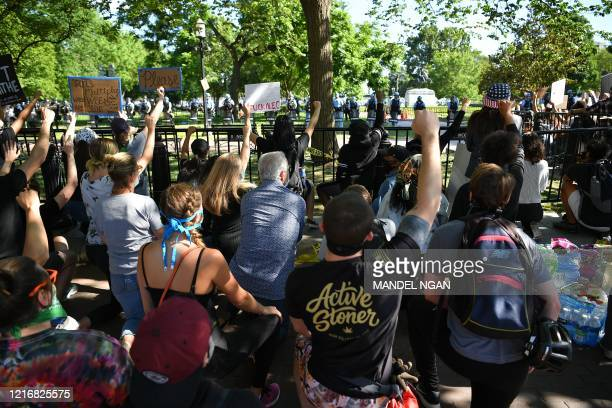 Protestors take a knee and raise their fists in Lafayette Square near the White House in Washington DC on June 1 2020 Police fired tear gas outside...