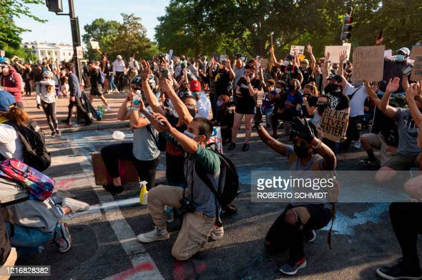 Protestors take a knee and raise their hands as they face riot police near the White House on June 1 2020 as demonstrations against George Floyd's...