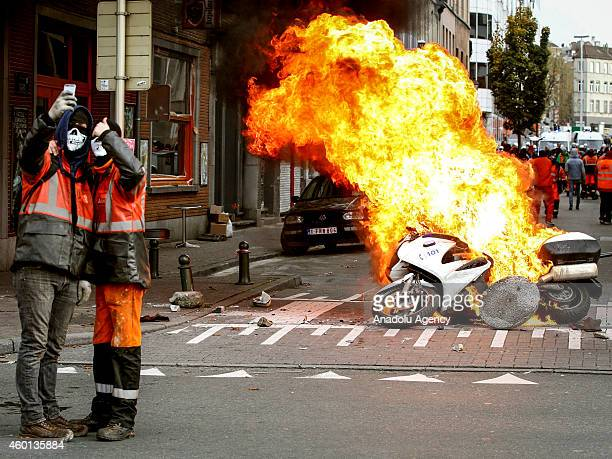 Protestors take a selfie in front of burning police motorbike in Brussels on November 6 2014 Belgians protest government's policies that will extend...