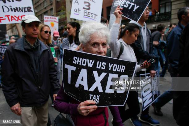 Protestors take part in the 'Tax March' calling on US President Donald Trump to release his tax records on April 15 2017 in New York Thousands of...