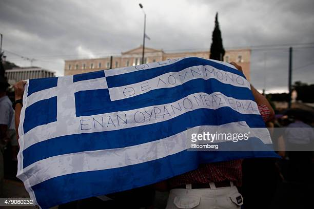 Protestors take shelter from rain under a Greek national flag that reads 'Greeks need only a sky full of stars' during a demonstration in support of...