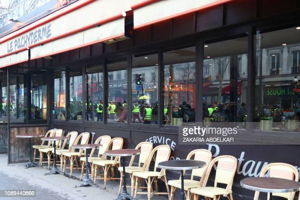 Protestors taking part in an antigovernment demonstration called by the Yellow Vests Gilets Jaunes movement are reflected in a bar window on the...