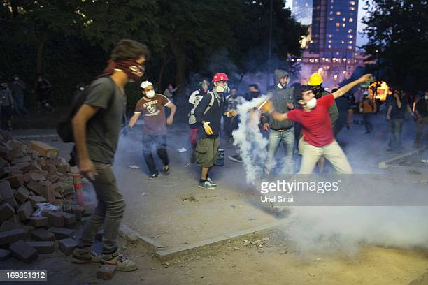Protestors throw a tear gas back at Turkish police during clashes near Turkish prime minister Recep Tayyip Erdogan office, between Taksim and...