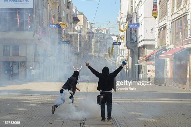 Protestors throw back tear gas canisters as they fight police to occupy Taksim Square June 1, 2013 in Istanbul, Turkey. People started peacefully...